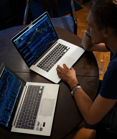 man looking at two computer screens